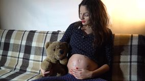 Ευτυχής έγκυος γυναίκα που στηρίζεται σε έναν καναπέ και που κτυπά την tummy φιλμ μικρού μήκους