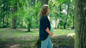 Ευτυχής έγκυος γυναίκα στον περίπατο εγκυμοσύνης του ένατου μήνα στο πάρκο και το χαμόγελο στο φως του ήλιου φιλμ μικρού μήκους