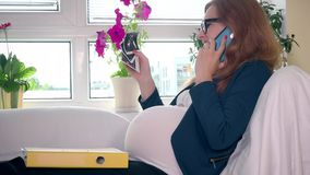 Ευτυχής έγκυος επιχειρησιακή γυναίκα με την εικόνα φωτογραφιών υπερήχου που καλεί το τηλέφωνο κυττάρων απόθεμα βίντεο