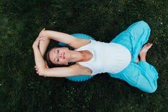 Ευτυχής έγκυος προγενέθλια μητρότητα γιόγκας που κάνει τις διαφορετικές ασκήσεις με το fitball στο πάρκο στη χλόη, Pilates Τοπ όψ Στοκ Εικόνες