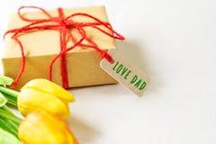Ευτυχής έννοια ημέρας πατέρων ` s Κιβώτιο δώρων και λουλούδι, ετικέττα εγγράφου με το κείμενο μπαμπάδων αγάπης Στοκ φωτογραφία με δικαίωμα ελεύθερης χρήσης