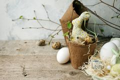 Ευτυχής έννοια Πάσχας - τα αυγά Πάσχας και το κουνέλι λαγουδάκι στην ασήμαντη και φρέσκια πρασινάδα τεχνών λουλουδιών διακλαδίζον στοκ φωτογραφία