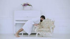 Ευτυχής έννοια πρωινού Το Hipster απολαμβάνει το πρωί τεντώνοντας τα όπλα και πιεσμένος κοντά στο πιάνο και την παλαιά πολυθρόνα  απόθεμα βίντεο