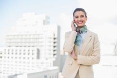 Ευτυχής έξυπνη καφετιά μαλλιαρή επιχειρηματίας που κάνει ένα τηλεφώνημα Στοκ Φωτογραφίες