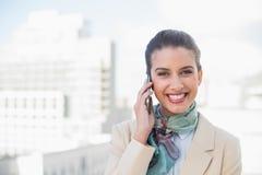 Ευτυχής έξυπνη καφετιά μαλλιαρή επιχειρηματίας που κάνει ένα τηλεφώνημα Στοκ φωτογραφία με δικαίωμα ελεύθερης χρήσης