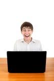 Ευτυχής έφηβος πίσω από το lap-top Στοκ φωτογραφία με δικαίωμα ελεύθερης χρήσης