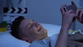 Ευτυχής έφηβος που προσέχει τα αστεία βίντεο στο smartphone και το γέλιο, που βρίσκονται στο κρεβάτι απόθεμα βίντεο