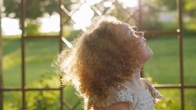 Ευτυχής ήλιος ρύθμισης γέλιου μικρών κοριτσιών Σγουρό κορίτσι στο φως ηλιοβασιλέματος απόθεμα βίντεο
