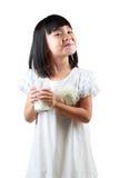 Ευτυχής λίγο ασιατικό κορίτσι που κρατά ένα φλυτζάνι του γάλακτος Στοκ Φωτογραφίες