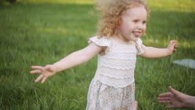Ευτυχής λίγο κορίτσι παιδιών σε ένα άσπρο φόρεμα που τρέχει επάνω στον πράσινο τομέα λιβαδιών φιλμ μικρού μήκους