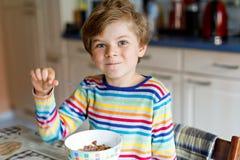 Ευτυχής λίγο ξανθό αγόρι παιδιών που τρώει τα δημητριακά για το πρόγευμα ή το μεσημεριανό γεύμα Υγιής κατανάλωση για τα παιδιά Στοκ φωτογραφία με δικαίωμα ελεύθερης χρήσης