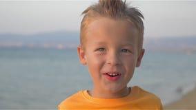 Ευτυχής λίγο παιδί που κοιτάζει στη κάμερα και το χαμόγελο φιλμ μικρού μήκους