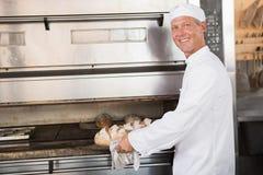 Ευτυχής δίσκος εκμετάλλευσης αρτοποιών του φρέσκου ψωμιού Στοκ εικόνες με δικαίωμα ελεύθερης χρήσης