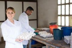 Ευτυχής δίσκος χαρτοκιβωτίων εκμετάλλευσης γυναικών με τα φρέσκα αυγά Στοκ φωτογραφία με δικαίωμα ελεύθερης χρήσης