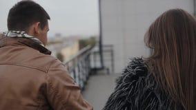 Ευτυχής αγάπη Backview ενός σκοτεινός-μαλλιαρού ζεύγους, που περπατά σε μια στέγη, φίλημα Αρμονία σε σχέση φιλμ μικρού μήκους