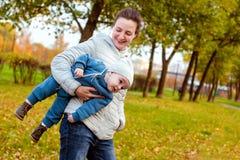 Ευτυχής αγαπώντας οικογένεια στο πάρκο Μητέρα στο λευκό και αγοράκι στο μπλε που έχει τη διασκέδαση, που παίζει και που γελά στη  στοκ εικόνα