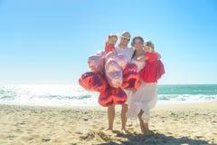 Ευτυχής αγκαλιάζοντας οικογένεια στην παραλία με τα μπαλόνια Στοκ εικόνες με δικαίωμα ελεύθερης χρήσης