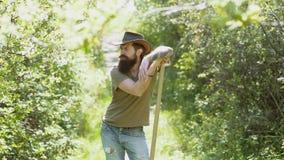 Ευτυχής αγρότης που έχει τη διασκέδαση στον τομέα άνοιξη Ζωή Eco Πορτρέτο του όμορφου νέου γενειοφόρου ατόμου στο υπόβαθρο άνοιξη απόθεμα βίντεο