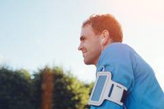 Ευτυχής αθλητής με armband τη μουσική ακούσματος στο πάρκο Στοκ Εικόνες