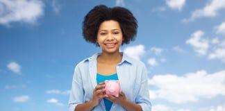 Ευτυχής αμερικανική νέα γυναίκα afro με τη piggy τράπεζα Στοκ Εικόνα