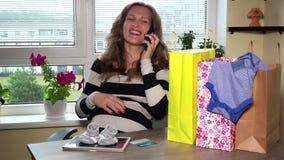 Ευτυχής αναμένουσα μητέρα με το τηλέφωνο μετά από τις επιτυχείς αγορές στο διαδίκτυο on-line φιλμ μικρού μήκους