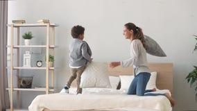 Ευτυχής αναμιγνύω-φυλή mom και γιος που έχει την πάλη μαξιλαριών στο κρεβάτι απόθεμα βίντεο