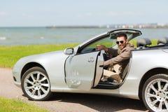 Ευτυχής ανοίγοντας πόρτα ατόμων του αυτοκινήτου καμπριολέ υπαίθρια Στοκ Φωτογραφίες