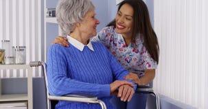Ευτυχής ανώτερη γυναίκα με το φιλικό μεξικάνικο caregiver στοκ εικόνα