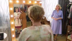 Ευτυχής ανώτερη γυναίκα που δοκιμάζει το νέο παλτό στο δωμάτιο συναρμολογήσεων του καταστήματος μόδας Εύθυμη ώριμη γυναίκα που κο απόθεμα βίντεο