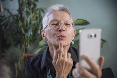 Ευτυχής ανώτερη γυναίκα που στέλνει το φιλί πέρα από το skype Στοκ φωτογραφία με δικαίωμα ελεύθερης χρήσης