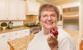 Ευτυχής ανώτερη ενήλικη γυναίκα με την κόκκινη Apple μέσα στην κουζίνα Στοκ φωτογραφία με δικαίωμα ελεύθερης χρήσης