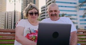 Ευτυχής ανώτερη συνεδρίαση ζευγών σε έναν πάγκο το καλοκαίρι σε μια σύγχρονη πόλη με ένα lap-top μεταξύ των φοινίκων απόθεμα βίντεο