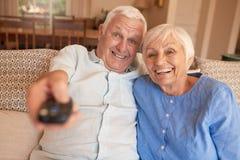 Ευτυχής ανώτερη τηλεόραση προσοχής ζευγών μαζί στον καναπέ τους Στοκ Εικόνα