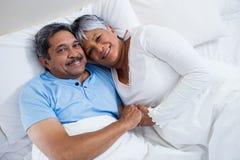 Ευτυχής ανώτερη χαλάρωση ζευγών στο κρεβάτι στην κρεβατοκάμαρα Στοκ φωτογραφίες με δικαίωμα ελεύθερης χρήσης