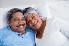 Ευτυχής ανώτερη χαλάρωση ζευγών στο κρεβάτι στην κρεβατοκάμαρα Στοκ Εικόνες