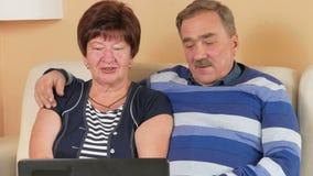 Ευτυχής ανώτερος άνδρας και μια γυναίκα που προσέχει τον κινηματογράφο στο lap-top Αγκαλιάζουν και συζητούν τι συμβαίνει στην οθό απόθεμα βίντεο
