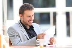 Ευτυχής ανώτερος υπάλληλος που διαβάζει μια επιστολή σε έναν φραγμό Στοκ εικόνα με δικαίωμα ελεύθερης χρήσης