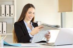 Ευτυχής ανώτερος υπάλληλος που διαβάζει μια εφημερίδα στο γραφείο Στοκ φωτογραφία με δικαίωμα ελεύθερης χρήσης