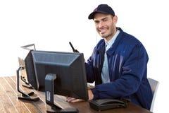 Ευτυχής αξιωματικός ασφαλείας που μιλά walkie-talkie χρησιμοποιώντας τον υπολογιστή στοκ εικόνες