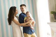 ευτυχής απομονωμένη μητέρα οικογενειακών πατέρων ανασκόπησης μωρών πέρα από τις χαμογελώντας λευκές νεολαίες Στοκ Εικόνα
