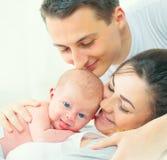 ευτυχής απομονωμένη μητέρα οικογενειακών πατέρων ανασκόπησης μωρών πέρα από τις χαμογελώντας λευκές νεολαίες Πατέρας, μητέρα και  Στοκ εικόνα με δικαίωμα ελεύθερης χρήσης