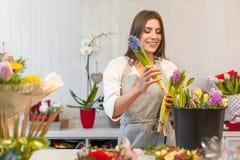Ευτυχής απόλαυση κοριτσιών ανθοκόμων που λειτουργεί με τα λουλούδια στοκ φωτογραφίες
