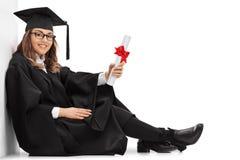 Ευτυχής απόφοιτος φοιτητής με μια συνεδρίαση διπλωμάτων στο πάτωμα Στοκ φωτογραφία με δικαίωμα ελεύθερης χρήσης