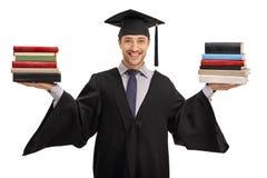 Ευτυχής απόφοιτος φοιτητής που κρατά δύο σωρούς των βιβλίων Στοκ Εικόνες