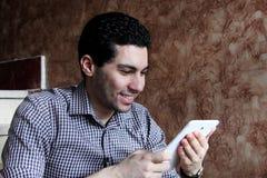 Ευτυχής αραβικός επιχειρηματίας με το τηλέφωνο και την ταμπλέτα Στοκ Εικόνα