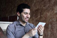 Ευτυχής αραβικός επιχειρηματίας με το τηλέφωνο και την ταμπλέτα Στοκ Εικόνες