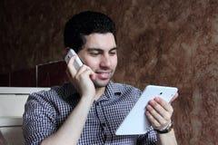 Ευτυχής αραβικός επιχειρηματίας με το τηλέφωνο και την ταμπλέτα Στοκ φωτογραφία με δικαίωμα ελεύθερης χρήσης