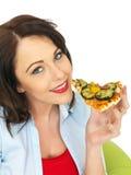 Ευτυχής αρκετά νέα γυναίκα που τρώει μια φέτα της πρόσφατα ψημένης χορτοφάγου πίτσας στοκ φωτογραφία με δικαίωμα ελεύθερης χρήσης