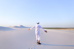Ευτυχής αρσενικός Άραβας περπατά κατά μήκος της άσπρης ερήμου άμμου και χαίρεται για το ΝΕ Στοκ Εικόνες