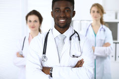 Ευτυχής αρσενικός γιατρός αφροαμερικάνων με το ιατρικό προσωπικό στο νοσοκομείο Στοκ εικόνες με δικαίωμα ελεύθερης χρήσης
